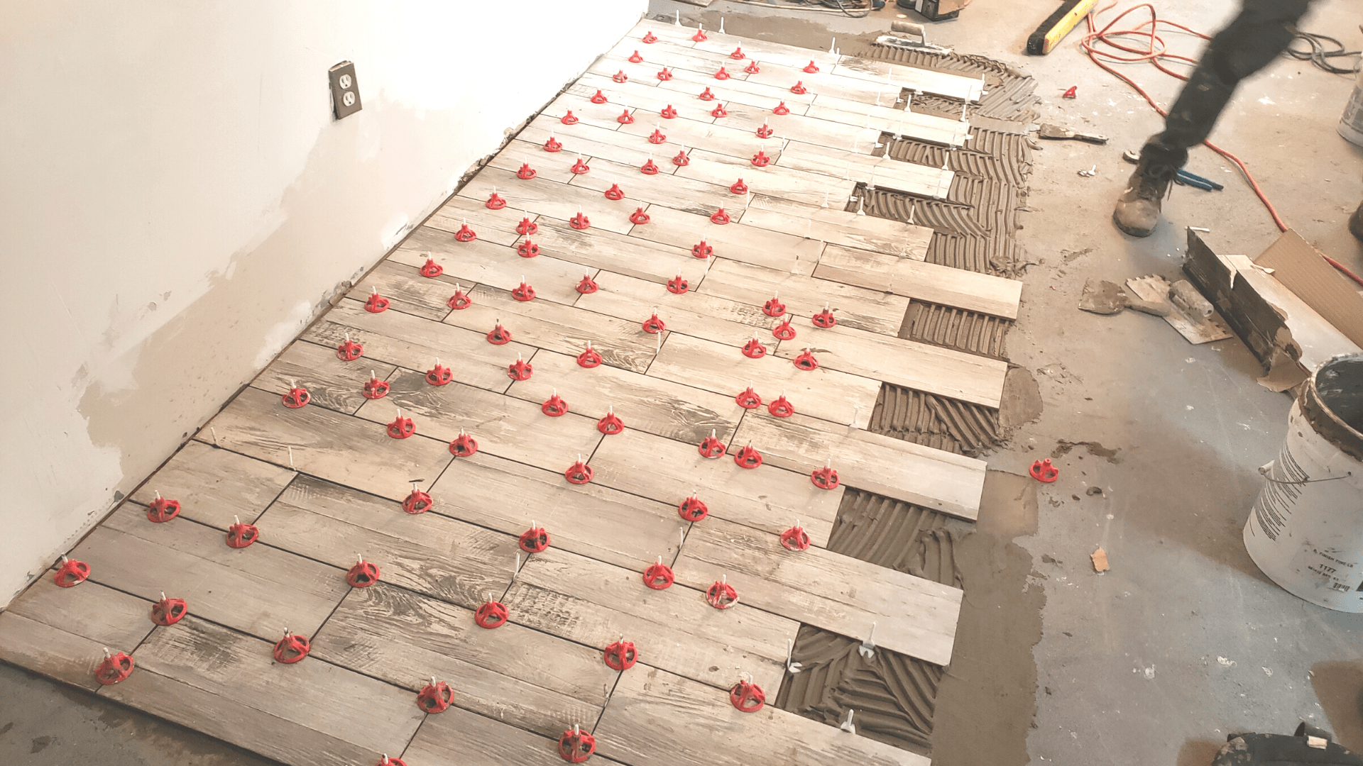 Spin doctor tile levling system being used on an in-progress tile floor